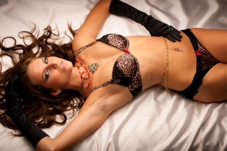 Beautiful young woman lying in bed photo