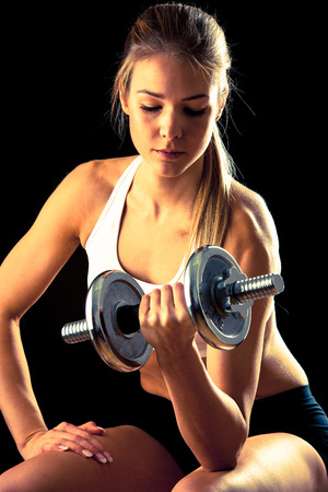 attractive young woman working out with dumbbells photo