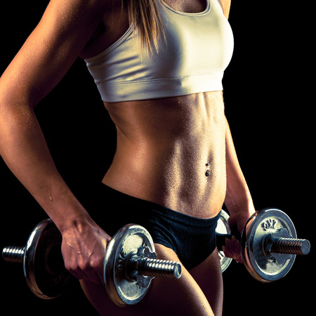attractive young woman working out with dumbbells
