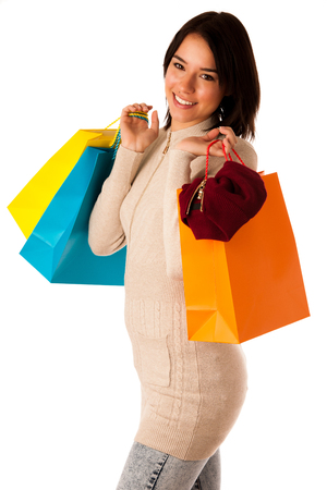 Attractive asian caucasian woman with shopping bags and credit card in her hands isolated over white  photo