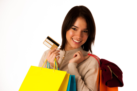 Attractive asian caucasian woman with shopping bags and credit card in her hands isolated over white background  photo