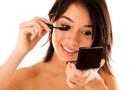 Pretty woman applying mascara on her eyelashes  photo