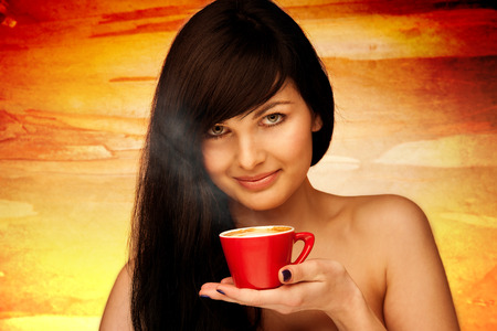 tive young woman with black hair holding red cup of coffee in her hand in the morning photo