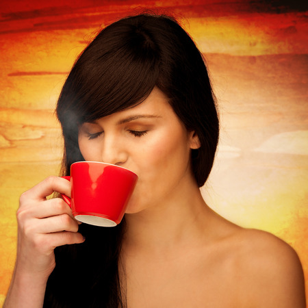 tive young woman with black hair holding red cup of coffee in her hand in the morning Stock Photo - 27331397
