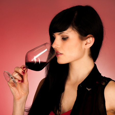 Beautiful young woman holding a glass of red wine over red background photo
