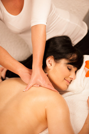 Beautiful young woman enjoing a massage treatment in wellness center Stock Photo - 27874566