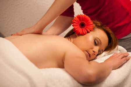 Beautiful young woman enjoing a massage treatment in wellness center photo