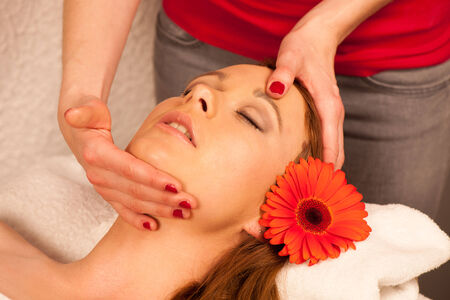 Woman having face massage treatment in wellness center photo