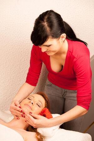 Woman having face massage treatment in wellness center