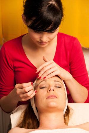 depilacion con cera: Cara de la mujer que tiene tratamiento de la piel en el centro de bienestar