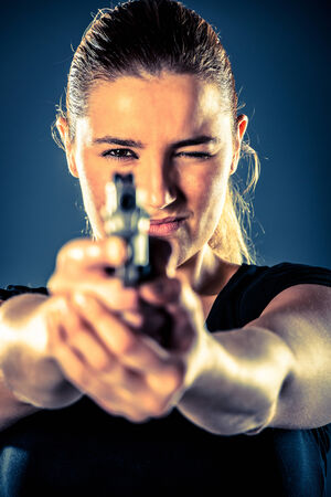Dangerous woman terrorist dressed in black with a gun in her hands photo