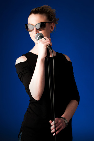 Woman singer on bluue background with microphone singing photo