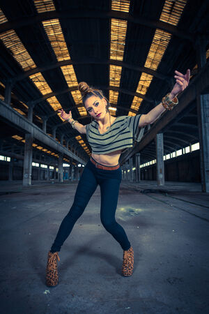 Hip hop dancer in an abandoned industrial hall in background photo