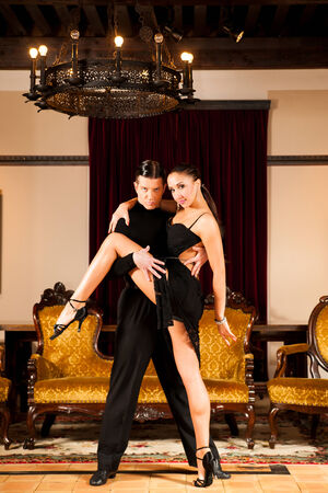 Young dance couple preforming latin show dance in beautiful ancient ballroom photo
