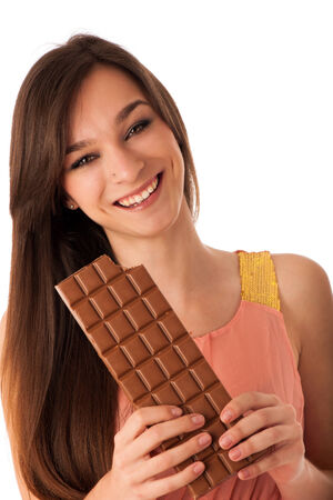 Beautiful young caucasian woman eating chocolate isolated over white background photo
