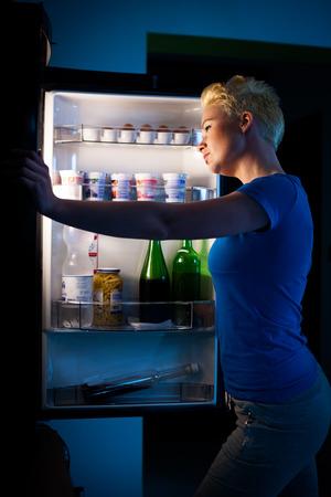 Hongerige vrouw op zoek naar voedsel in refregirator laat op de avond
