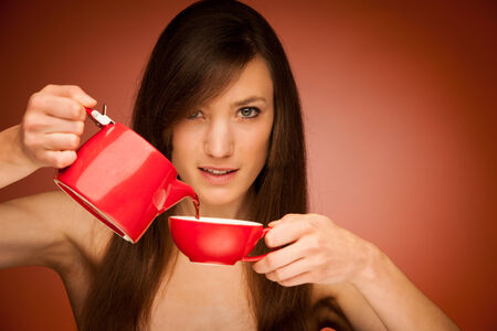 Beautiful young woman with tea pot and mug in her nhands iver warm background photo