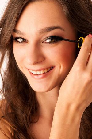 Peautiful hispanic woman applying mascara on her eyelashes isolated over white photo