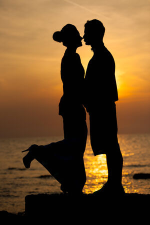 Silhouette of romantic couple on the beach at sunset photo