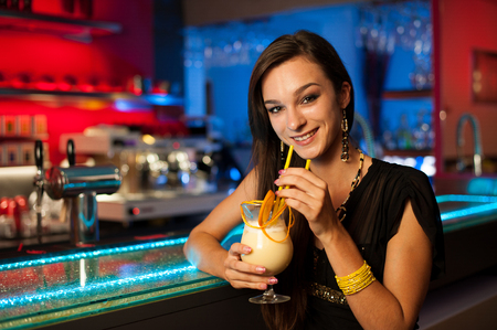 Girl drinks a cocktail in night club photo