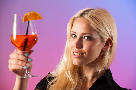 terracing: Beautiful young woman drinking aperol spritz isolated over colorful background Stock Photo