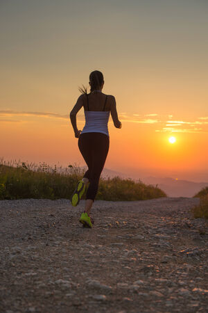 woman running outdoor on a mountain road at summer sunset photo