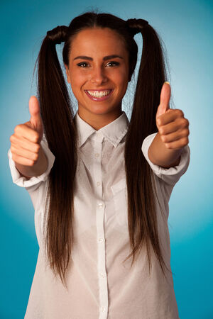 Beautiful hispanic business woman gesturing success shownig thumb up over blue background photo