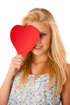 Beautiful young blonde woman with blue eyes holding red hart banner for valentines day isolated over white photo
