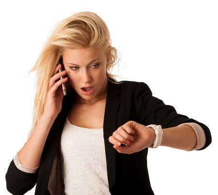 Mujer rubia joven que mira su reloj cuando ella está siendo tardía aislada sobre fondo blanco Foto de archivo