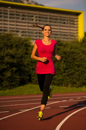 Preety young woman running on a track on a summer afternoon Stock Photo
