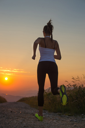 woman running outdoor on a mountain road at summer sunset