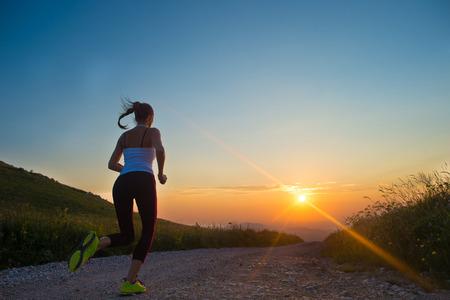 Frau läuft im Freien auf einer Bergstraße im Sommer Sonnenuntergang
