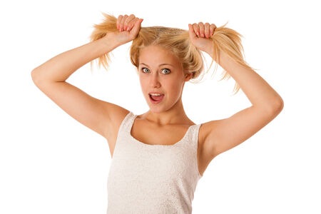 stres: Beautiful young blonde woman holds hair in her hand gesturing excitement isolated over white background