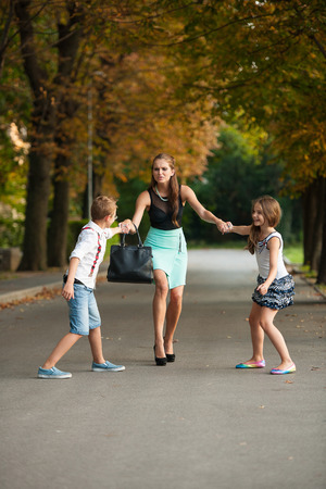 embarassed: Mother with naughti son adn daughter on a walk in park on summer evening
