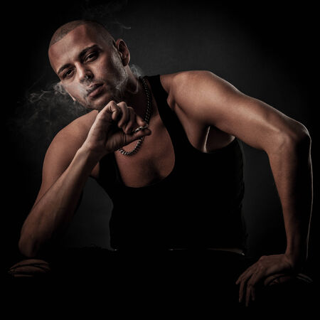 Handsome young man smokes cigarette in darkness - photography of unhealthy adicction photo