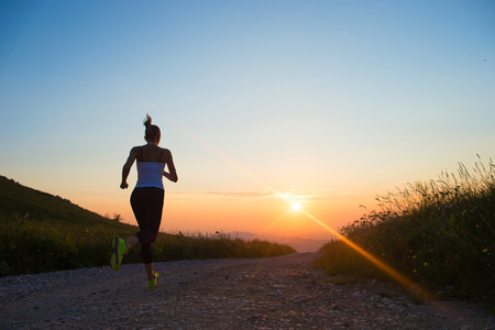 run woman: woman running outdoor on a mountain road at summer sunset