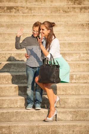 Mother and son walk on stairs in city on late sunny summer afternoon photo