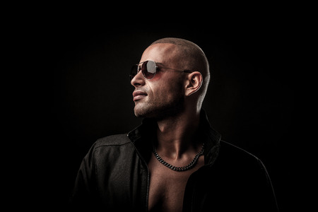 Dark photos of a mysteryous young man with sunglasses photo
