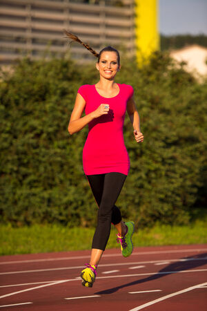 preety: Preety young woman running on a track on a summer afternoon Stock Photo