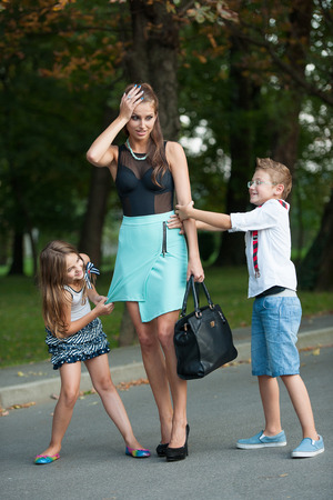 embarassed: Mother with naughty son and daughter on a walk in park on summer evening
