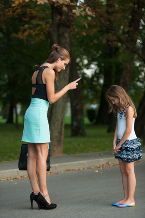 Mother talking to naughty daughter on a street in park