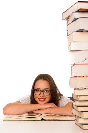Happy asian caucasian girl study with lots of books on the table isolated photo
