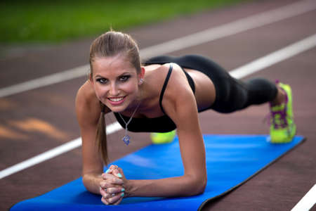 Woman working out on athlete track on summer afternoon photo