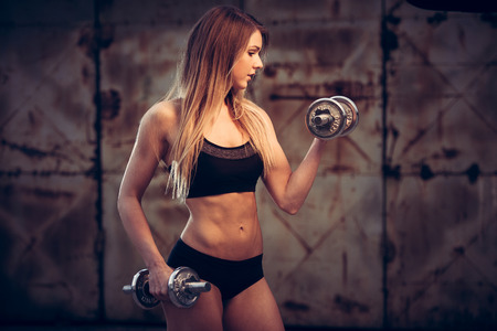 attractive young woman working out with dumbbells - bikini fitness girl with healthy lifestyle and perfect body photo