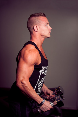 Hnadsome young man working out with dumbbells in fitness -  power training photo