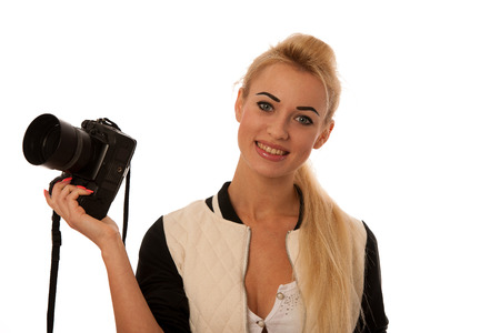 Woman holding a camera taking photos isolated over white background photo