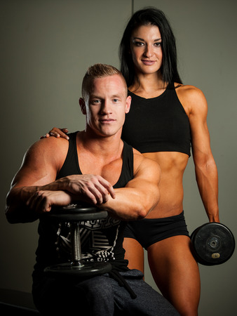 Fitness couple - woman and man with dumbbells in gym photo