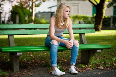 teenager thinking: Hermosa Woamn rubia descansa en el banco en el parque