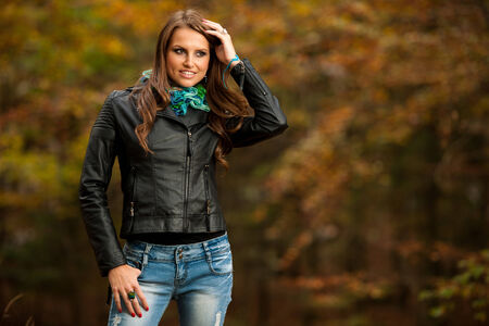 Pretty young woman on a walk in forest on late autumn day in fashoinable dress photo