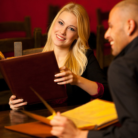 Young couple ordeting food in restaurant reading menu and deciding photo